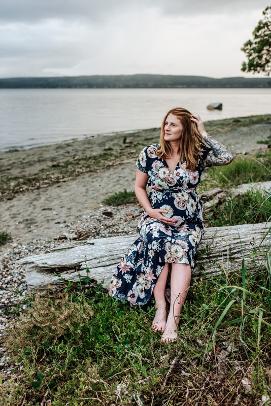 Maternity Photography - Maternity Photographer - Woman in floral dress holding her belly and sitting on a log
