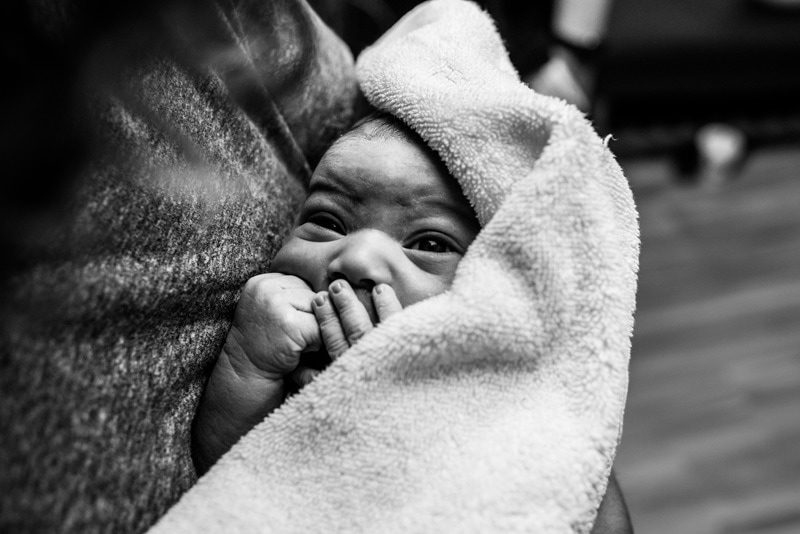 Birth Photography - Birth Photographer - newborn baby looking out from towel