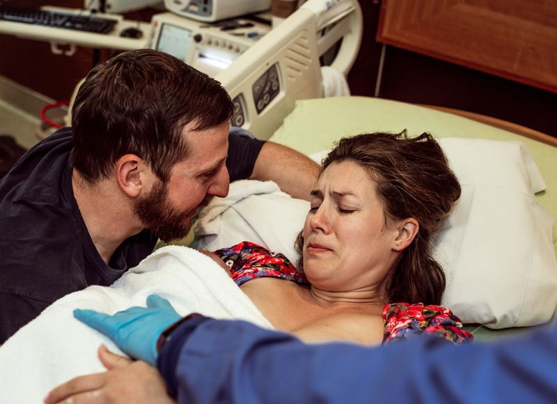Birth Photography - Birth Photographer - husband talking to wife right after birth
