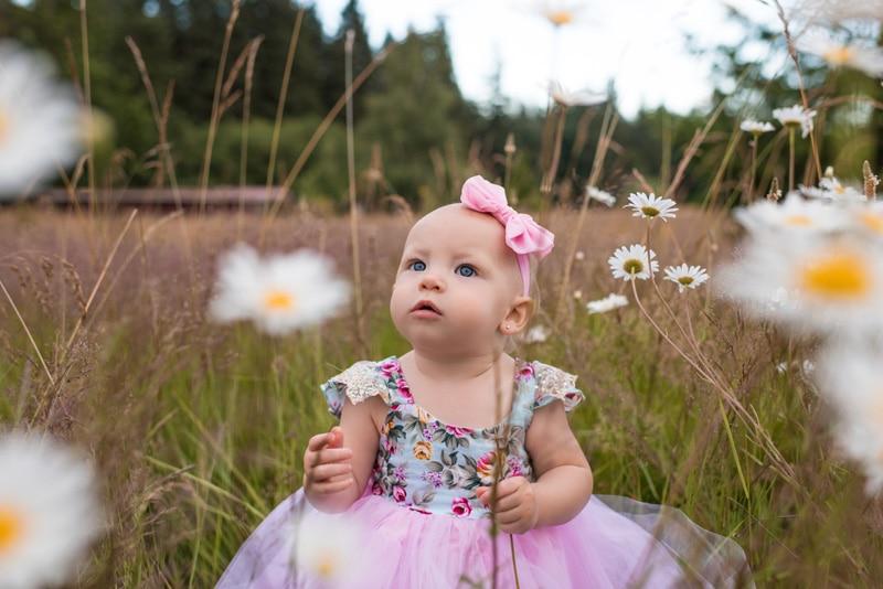Children Photography - Children Photographer - baby girl sitting among the flowers