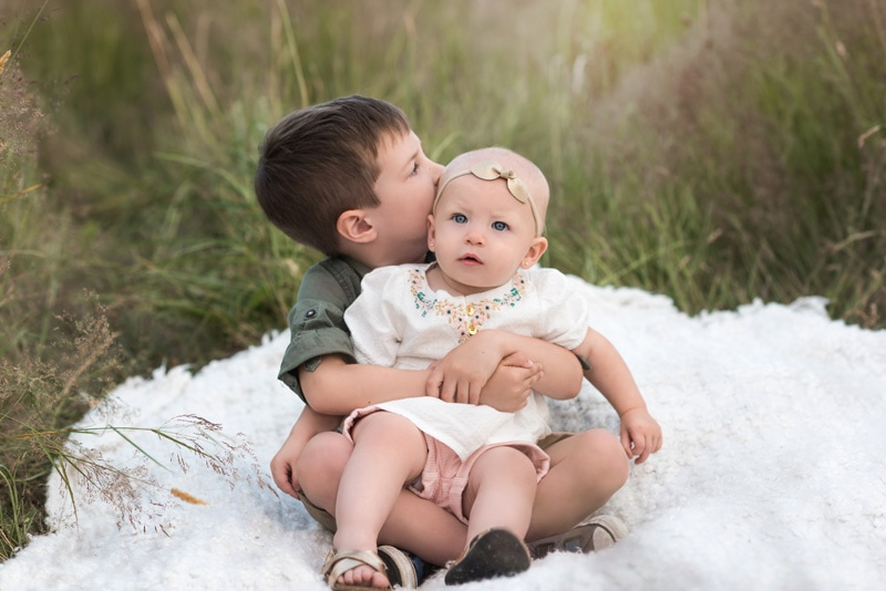 Children Photography - Children Photographer - baby girl sitting on brother's lap